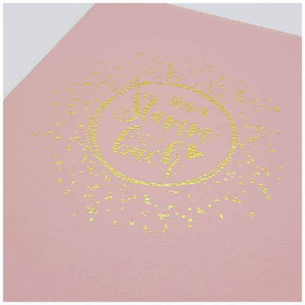 Goldprägung auf rosa Leder